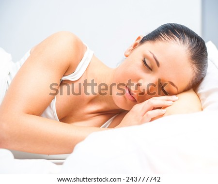 young beautiful woman sleeping in white bed at home - stock photo
