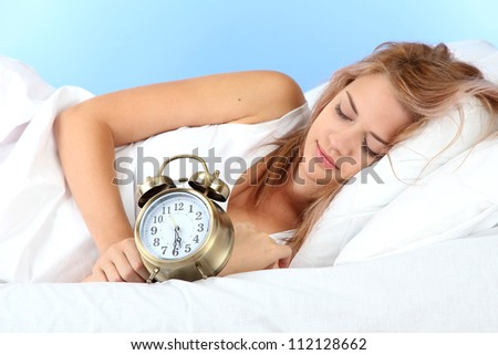 young beautiful woman sleeping on bed with alarm clock on blue background - stock photo