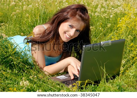 Young beautiful woman smiles while having fun with her laptop.
