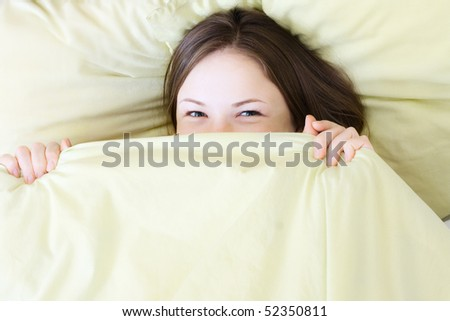 young beautiful woman smiling in the bed - stock photo