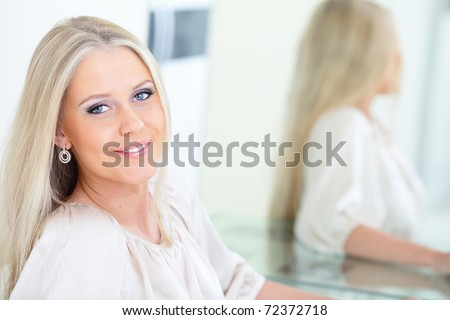 Young beautiful woman smiling near the mirror