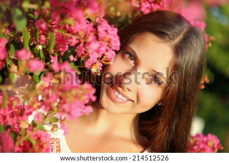 Young beautiful woman smiling near tree with pink flowers - stock photo
