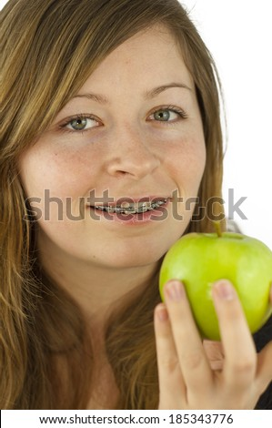 Young beautiful woman smiling with braces holding a green tasty apple isolated on white background  - stock photo