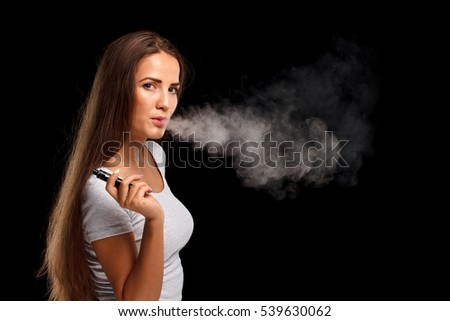Young beautiful woman smoking ( vaping ) e-cigarette