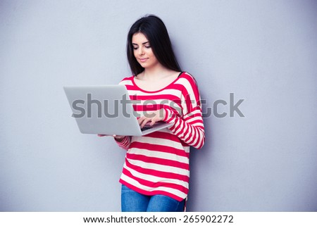 Young beautiful woman standing and typing on the laptop pver gray background. Looking on the laptop - stock photo