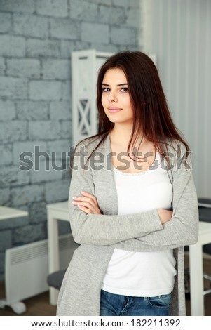 Young beautiful woman standing at office