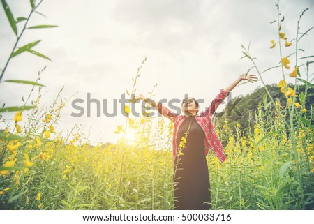 Young beautiful woman standing in the flower field enjoyment.