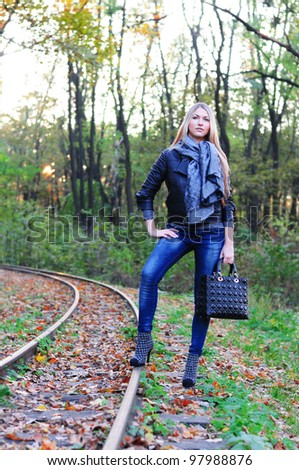 Young beautiful woman standing on a fall railroad - stock photo