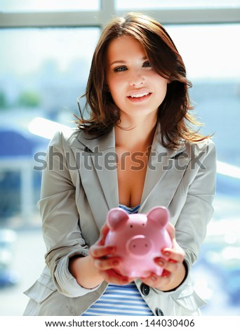Young beautiful woman standing with piggy bank (money box) - stock photo