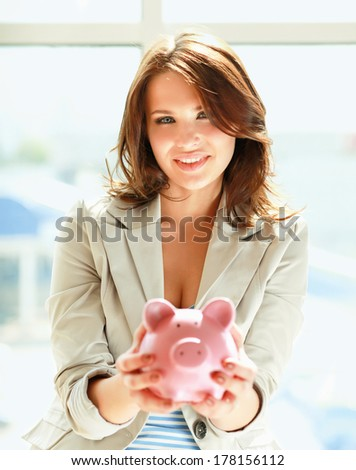 Young beautiful woman standing with piggy bank (money box), on building - stock photo