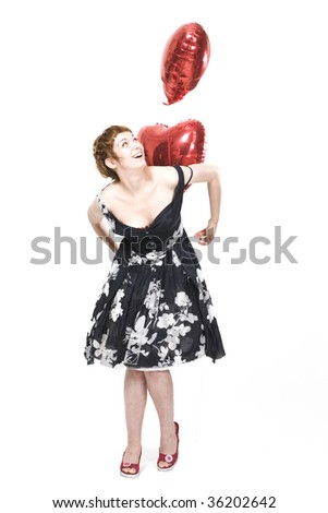 Young beautiful woman standing with red heart-shape helium balloon, isolated on white background