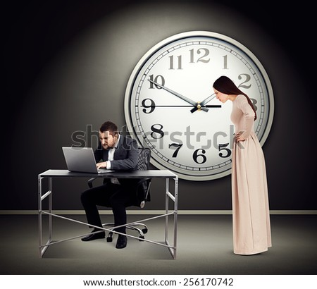 young beautiful woman staring at man with laptop. photo in dark room with big white clock on the wall