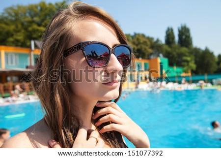 Young beautiful woman sunbathing near the pool - stock photo