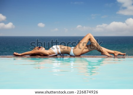 Young beautiful woman sunbathing. Nice sea view from swimming pool. - stock photo