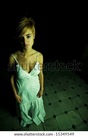 Young beautiful woman surrounded by darkness - stock photo
