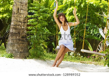 young beautiful woman swinging on natural background
