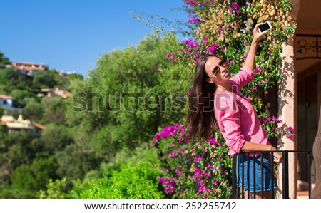 Young beautiful woman take photo on her phone at balcony - stock photo