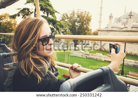 Young beautiful woman taking selfie photo in tourist bus near Blue Mosque in Istanbul, Turkey - stock photo