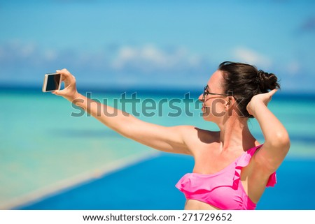 Young beautiful woman taking selfie with phone outdoors during beach vacation - stock photo
