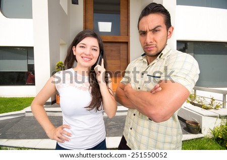 young beautiful woman talking on the phone outside her house while unhappy husband looks at her - stock photo