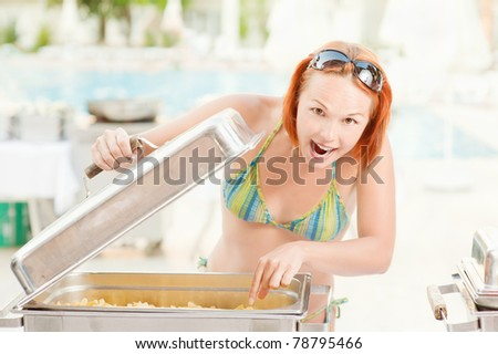 Young beautiful woman tastes food about summer pool on resort. - stock photo