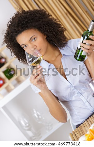 young beautiful woman tasting white wine at the restaurant