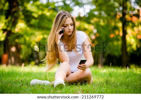 Young beautiful woman (teen girl) with 2 mobile phones - mobility concept - stock photo