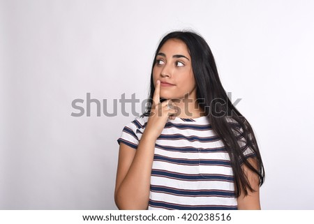 Young beautiful woman thoughtful in studio. Isolated white background. - stock photo
