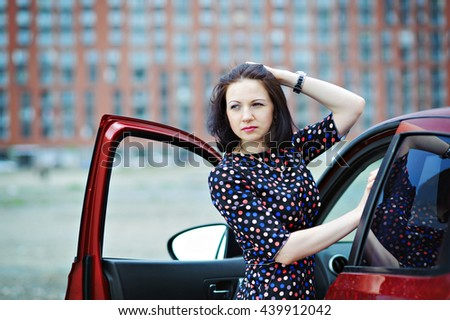 Young beautiful woman thoughtfully looking to the side, standing near the car. - stock photo