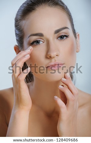 Young beautiful woman touching her face and applying moisturizer to her skin - stock photo