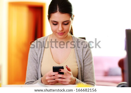 Young beautiful woman typing on smartphone at home - stock photo
