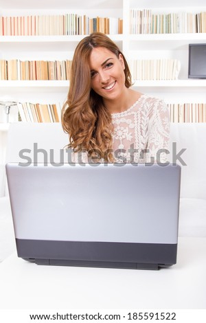 young beautiful woman using a laptop computer at home and looking in camera