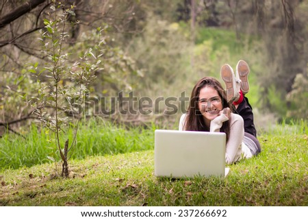 Young beautiful woman using a laptop computer at the park. - stock photo