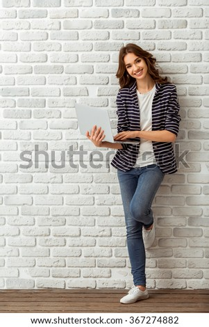Young beautiful woman using a laptop, dressed in a striped jacket and blue trousers on background brick wall - stock photo
