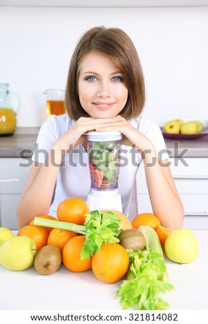 Young beautiful woman using blender, preparing orange juice - stock photo
