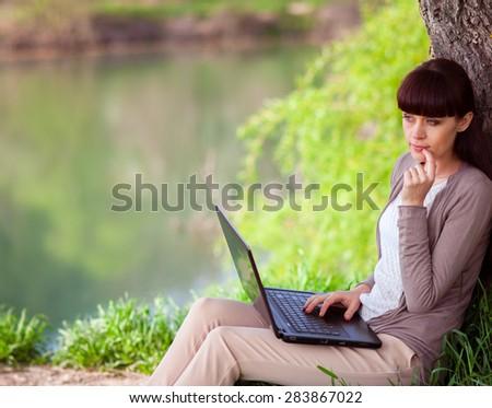 Young beautiful woman using laptop near lake - stock photo