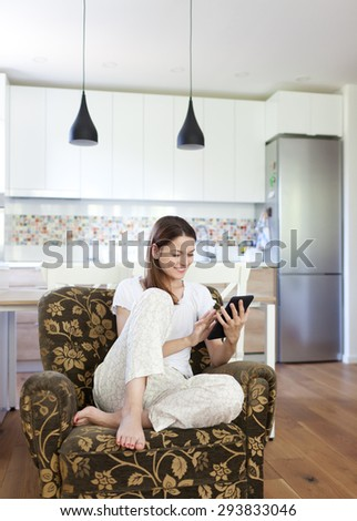 Young beautiful woman using tablet and relaxing in the armchair - stock photo