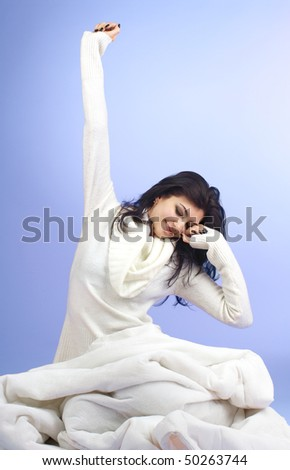 Young beautiful woman waking up over blue background - stock photo