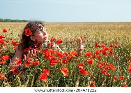 Young beautiful woman walking and dancing through a poppy field - stock photo