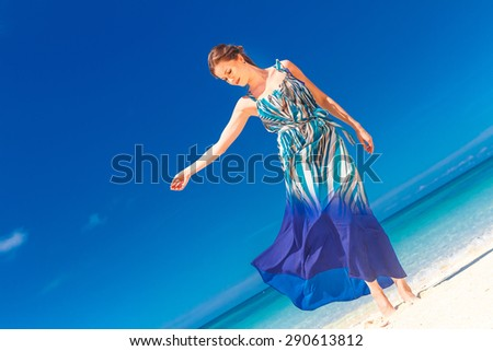 young beautiful woman walking by tropical sand beach, summer vacation - stock photo