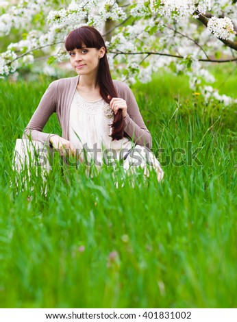 Young beautiful woman walking in blooming garden
