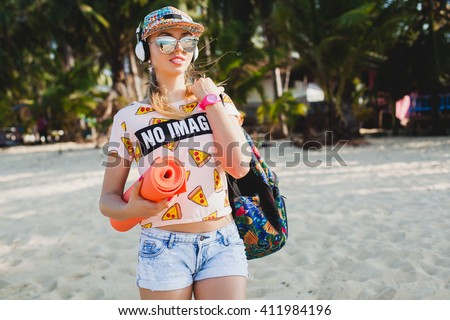 young beautiful woman walking on beach with yoga mat, listening to music on headphones, hipster sport swag style, denim shorts, t-shirt, backpack, cap, sunglasses, sunny, summer weekend, happy  - stock photo
