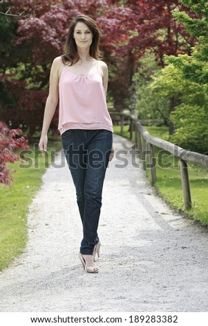 Young beautiful woman walking on the path in the park next to the fence , beautiful woman walking on the road in a beautiful park