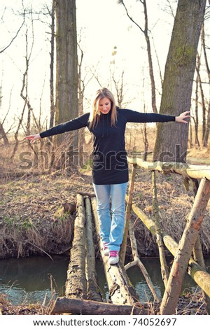 Young beautiful woman walking on the thin foot bridge across the river in spring - stock photo