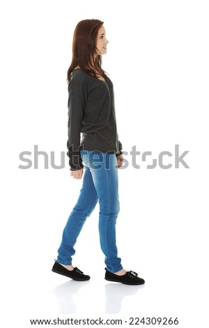 Young beautiful woman walking smiling - stock photo
