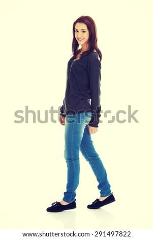 Young beautiful woman walking smiling - stock photo