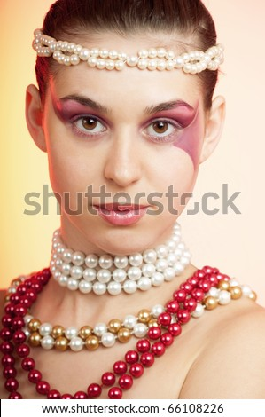Young beautiful woman wearing pearls around her neck nad forehead, dof is shallow - stock photo