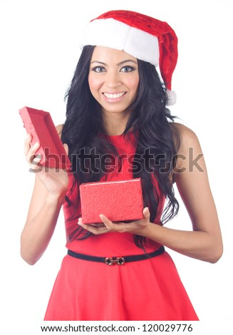 Young beautiful woman wearing santa hat opening gift box - stock photo