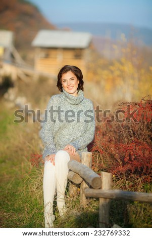 Young beautiful woman wearing warm knit clothes. Outdoors in sunlight. Model fashion shooting. Autumn, winter season. Leggings. Gaiters. Golfs.