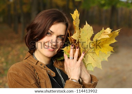 young beautiful woman with a bouquet of maple leaves - stock photo